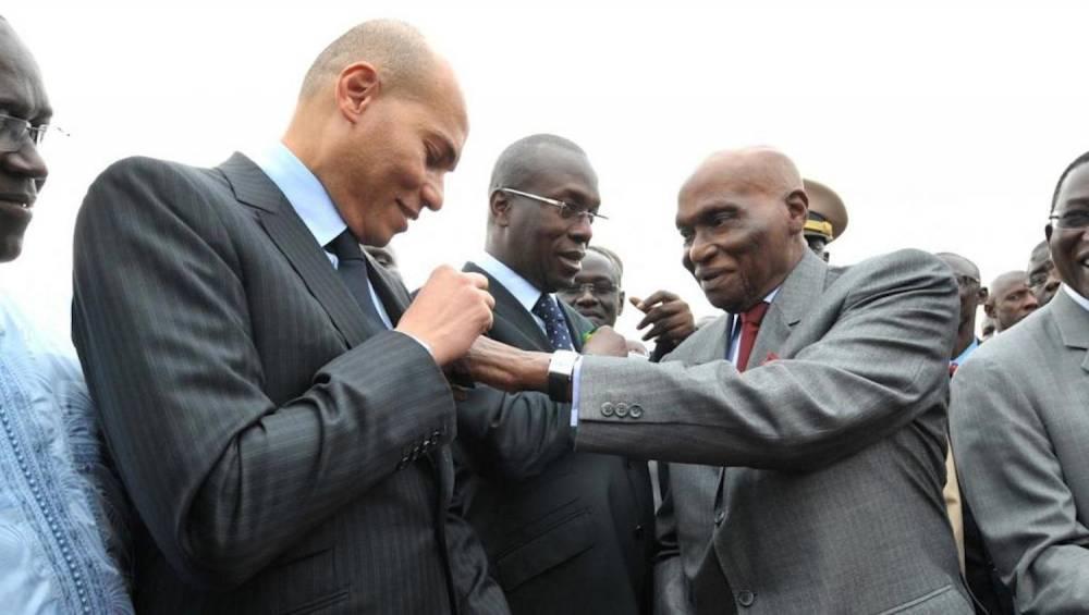 Le président Abdoulaye Wade ajuste un ruban sur le costume de son fils Karim Wade, le 19 janvier 2011. ©  AFP/Seyllou Diallo