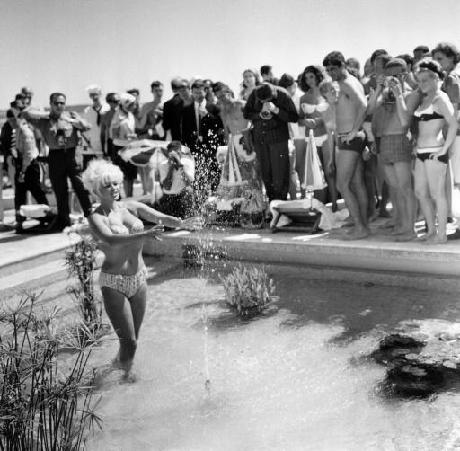 L'actrice américaine Jayne Mansfield pose pour les photographes dans le bassin de l'hotel Carlton, le 12 mai 1964, lors du Festival de Cannes ©  AFP/Archives