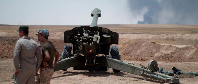 Artillerie irakienne tournée vers Qayyarah à 60 kilomètres au sud de Mossoul. De la ville s'élève la fumée des feux allumés par les troupes de l'État islamique dans les champs de pétrole pour se couvrir des frappes de la coalition, samedi 16 juillet 2016.