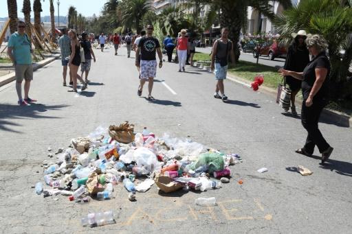 """Sous le message """"Lâche!"""" dessiné à la craie, des gens jettent des détritus le 18 juillet 2016 sur la promenade des Anglais à Nice, où un homme conduisant un camion a tué plus de 80 personnes le 14 juillet © Valery HACHE AFP"""