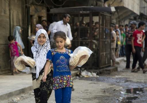 Deux jeunes filles portent des sacs de pain devant une boulangerie à Alep le 12 juillet 2016 © KARAM AL-MASRI AFP/Archives