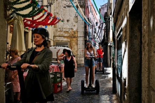 Des touristes circulent avec des Segways dans les ruelles du quartier Alfama de Lisbonne, le 29 juin 2016 © PATRICIA DE MELO MOREIRA AFP