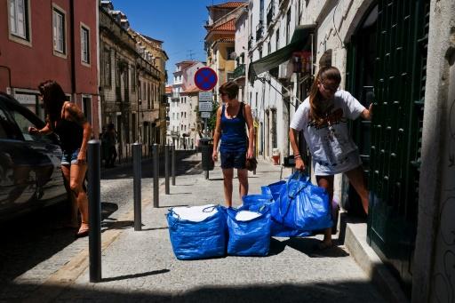 Carmo Pires (g) et ses deux filles portent des sacs de linge pour préparer des appartements pour les touristes à Alfama, quartier de Lisbonne, le 29 juin 2016 © PATRICIA DE MELO MOREIRA AFP