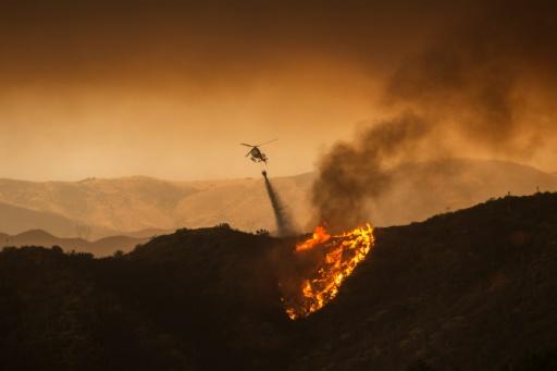 Un hélicoptère deverse de l'eau pour lutter contre un gigantesque incendie près de Santa Clarita en Californie, le 23 juillet 2016 © DAVID MCNEW AFP
