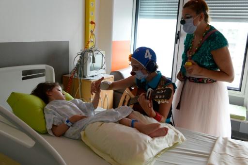 """Des clowns de l'association """"Le Rire Medecin"""" avec une enfant malade le 25 juillet 2016 à l'hôpital Necker à Paris © BERTRAND GUAY AFP"""