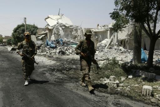 Des membres des Forces démocratiques syriennes (SDF) patrouillent parmi les décombres dans la ville de Minbej (nord de la Syrie) le 7 août 2016 recherchant les derniers jihadistes © DELIL SOULEIMAN AFP