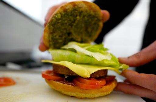 """Le chef Johannes Thenerl prépare un """"burger vegan"""" à L'Herbivore"""", restaurant vegan à  Berlin, le 29 avril 2016 © John MACDOUGALL AFP"""
