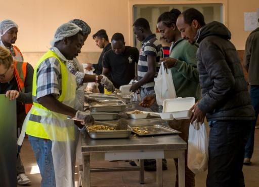 """Des migrants reçoivent la nourriture distribuée par l'association """"Vie Active"""" au centre d'aide humanitaire Jules-Ferry  proche de la """"Jungle"""" le 22 août 2016 à Calais © PHILIPPE HUGUEN AFP"""