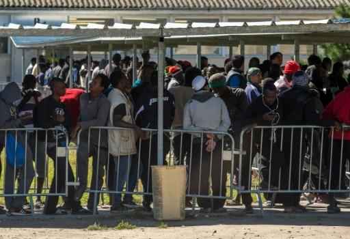 """Des migrants font la queue pour recevoir de la nourriture distribuée par l'association """"Vie Active"""" au centre d'aide humanitaire Jules-Ferry  proche de la """"Jungle"""" le 22 août 2016 à Calais © PHILIPPE HUGUEN AFP"""