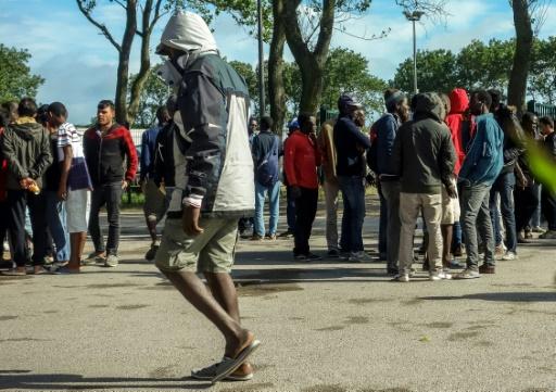 """Des migrants devant le centre d'aide humanitaire Jules-Ferry  proche de la """"Jungle"""" le 22 août 2016 à Calais © PHILIPPE HUGUEN AFP"""