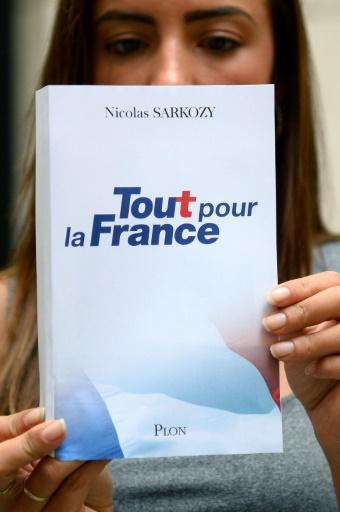 Une femme tient un exemplaire du livre de Nicolas Sarkozy à paraître mercredi, le 22 août 2016 à Paris © BERTRAND GUAY                        AFP