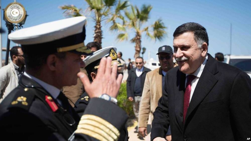 Le chef du gouvernement libyen d'union nationale (GNA) Fayez al-Sarraj, à droite, est salué par un officier de l'armée libyenne, à Tripoli, Libye, 30 mars 2016. ©  AP