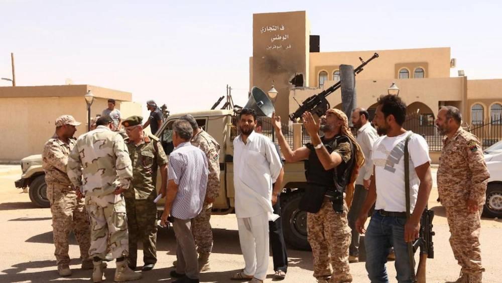 Des soldats de forces progouvernementales fêtent la reprise de la ville d'Abou Greïn, avec pour objectif la reconquête de Syrte, bastion de l'EI en Libye. ©  AFP/Mahmud Turkia