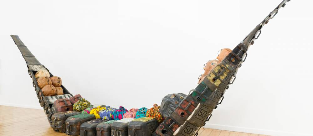 Romuald Hazoumè Cry of the Whale, (front of boat)  2016. Mixed media installation, 250 x 650 x 140 cm.  ©  Jonathan Greet/Courtesy October Gallery