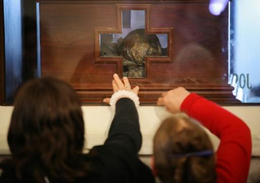 """Des fidèles touchent le reliquaire du Père José Gabriel Brochero (1840-1914), surnommé le """"curé gaucho"""", le 15 octobre 2016 à Cordoba, en Argentine © NICOLAS AGUILERA AFP"""