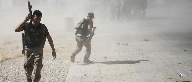Les forces spéciales irakiennes courent pour se mettre à couvert à Bartella, à l'est de Mossoul.