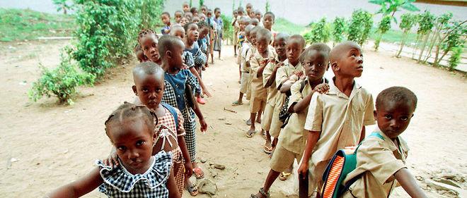 Des écoliers ivoiriens attendent en rang, d'un côté les filles, de l'autre les garçons, avant de rentrer en classe le 26 novembre 1999 dans une école primaire à yopougon, dans la banlieue d'Abidjan.