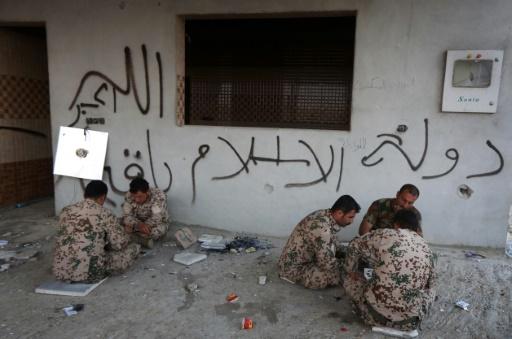 """Des peshmergas, combattants kurdes, devant une maison barrée de de slogan: """"L'Etat Islamique est éternel"""" dans un village près de Mossoul, en Irak, le 26 octobre 2016 © SAFIN HAMED AFP"""