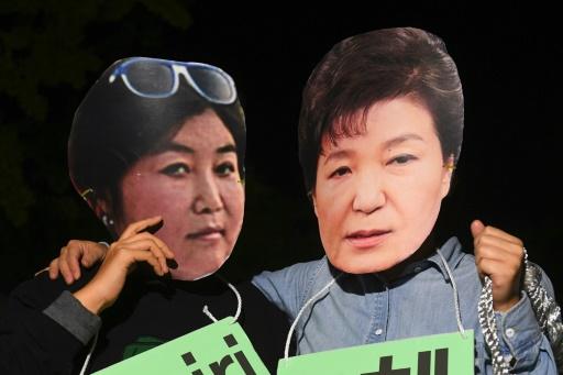 Des manifestants portant des masques de la présidente de Corée du sud Park Geun-Hye (d) et de son ex-confidente Choi Soon-Sil (g), dénoncent les liens entre elles lors d'un rassemblement à Séoul, le 27 octobre 2016 © JUNG YEON-JE AFP/Archives