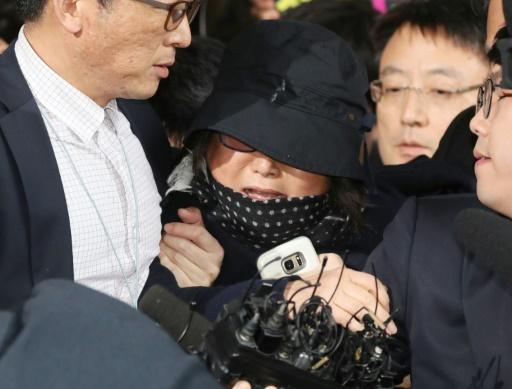 Choi Soon-Sil (c) tente de se frayer un passage, lors de son arrivée au tribunal à Séoul, le 31 octobre 2016 © Yonhap YONHAP/AFP