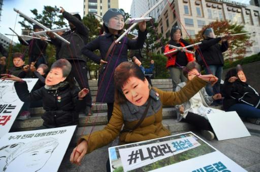 Des manifestants portent des masques à l'effigie de la présidente sud-coréenne Park Geun-Hye et de sa confidente Choi Soon-Sil à Séoul, le 29 octobre 2016 pour dénoncer un scandale de corruption impliquant les deux femmes © JUNG YEON-JE AFP