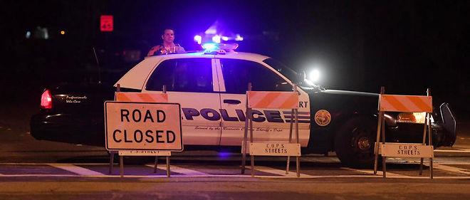 Une voiture de police bloque la route sur une scène de crime.
