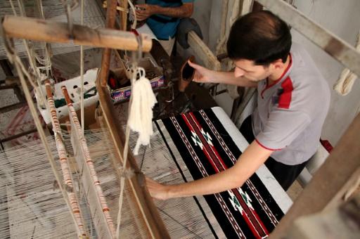 Abou Mostafa travaille sur son métier à tisser dans un atelier qui va bientôt fermer ses portes, à Ariha (70 km d'Alep), le 12 octobre 2016 © OMAR HAJ KADOUR AFP