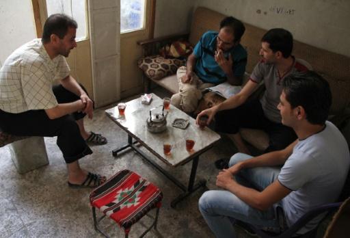 Abou Mohammed (2è g) et ses collègues Abou Mostafa (2è d) et Abou Ahmed font une pause dans leur atelier de tissage à Ariha, non loin d'Alep, le 12 octobre 2016 © OMAR HAJ KADOUR AFP
