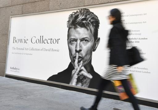 Une femme passe le 26 septembre 2016 à New York devant une publicité pour la vente aux enchères des oeuvres d'art du chanteur britannique décédé David Bowie © ANGELA WEISS AFP/Archives