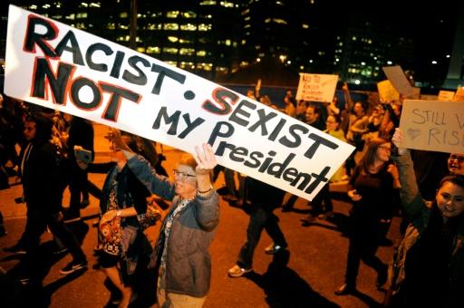 """Une manifestante brandit une pancarte dénonçant Trump """"raciste et sexiste, pas mon président"""" dans les rues de Denver, le 10 novembre 2016 © Jason Connolly AFP"""