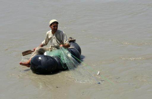 Un pêcheur pakistanais cherche des poissons à pêcher, assis sur une chambre à air, le 18 août 2016 sur la rivière Kaboul, près du village Hajji Zai (nord-ouest du Pakistan) © A MAJEED AFP