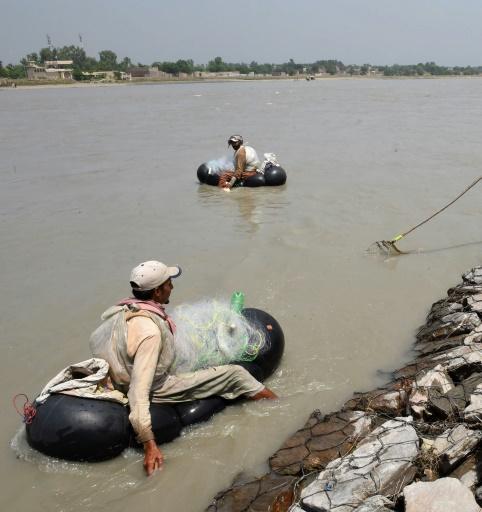 Sur des chambres à air gonflés des pêcheurs pakistanais sont à la recherche de poissons dans la rivière Kaboul, à Hajji Zai, village du nord-ouest du Pakistan © A MAJEED AFP