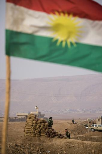 Un drapeau kurde flotte alors que les peshmergas gardent leur position sur une berge au nord du village de Shaqouli, à 35 kilomètres à l'est de Mossoul, le 10 novembre 2016 © Odd ANDERSEN AFP