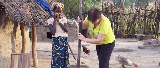 Une touriste s'essaie au maniement du pilon dans un village du Sénégal.