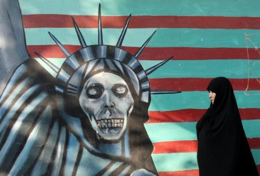Une Iranienne passe devant une peinture murale sur la façade de l'ancienne ambassade américaine à Téhéran, le 9 novembre 2016 © ATTA KENARE AFP