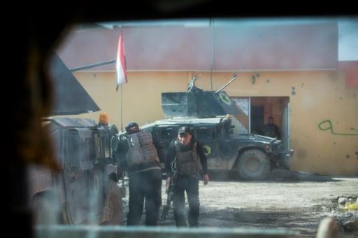 Une photo prise par la fenêtre blindé montre des soldats de la 2ème division des forces spéciales irakiennes se couvrant derrière leurs véhicules sous le feu d'un tireur de l'EI, le 12 novembre 2016, dans le quartier Al-Samah, à l'est de Mossoul © Odd ANDERSEN AFP