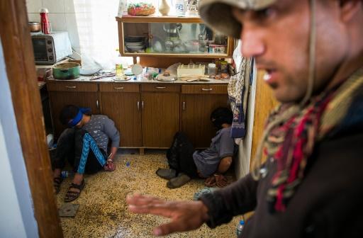 Un soldat de la 2e division des Forces Spéciales irakiennes garde deux hommes suspectés d'être des combattants de l'EI qui s'étaient cachés dans une maison, le 11 novembre 2016 dans le quartier Al-Samah, dans l'est de Mossoul © Odd ANDERSEN AFP