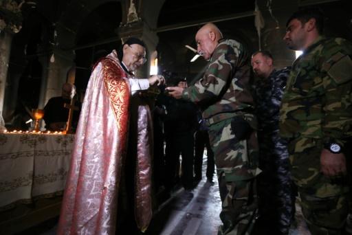 L'archevêque syro-catholique de Mossoul Yohanna Petros Mouche donne la communion aux forces chrétiennes irakiennes lors d'une messe dans l'église de l'Immaculée Conception le 30 octobre 2016 à Qaraqosh, reprise au groupe Etat islamique © SAFIN HAMED AFP/Archives