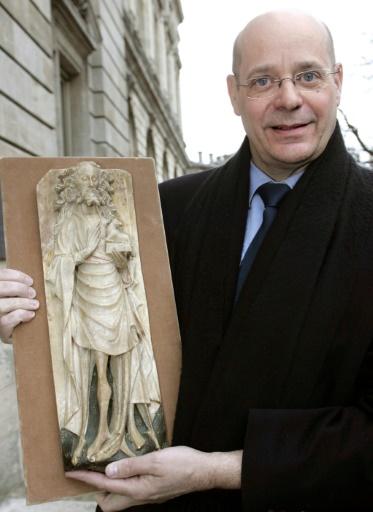 Christian Deydier, alors président du Syndicat national des antiquaires, tient une des statues retrouvées, le 2 mars 2006 à Bordeaux © MICHEL GANGNE AFP/Archives