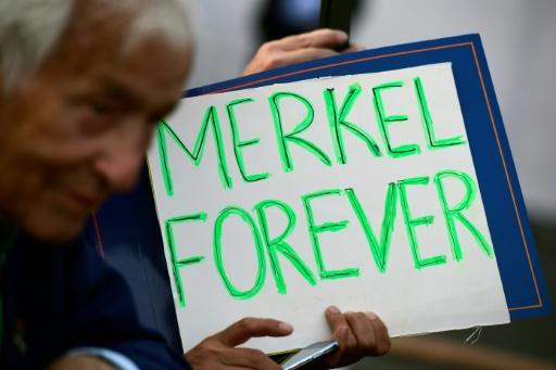 Un partisan d'Angela Merkel portant une pancarte lors d'une réunion politique le 14 septembre 2016 à Berlin © TOBIAS SCHWARZ AFP/Archives