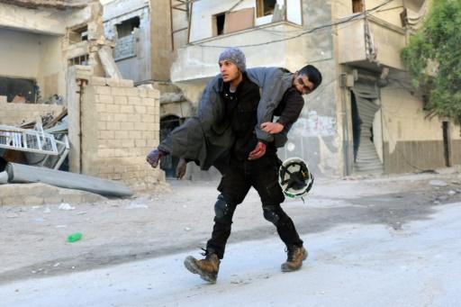 """Un Syrien membre de la sécurité civile (les """"casques blancs"""") porte un blessé, le 19 novembre 2016 dans un quartier rebelle d'Alep bombardé  © AMEER ALHALBI AFP"""