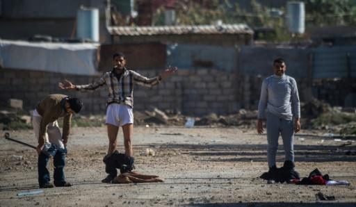 Des Irakiens se déshabillent avant d'approcher les forces spéciales à Mossoul, le 18 novembre 2016 © Odd ANDERSEN AFP