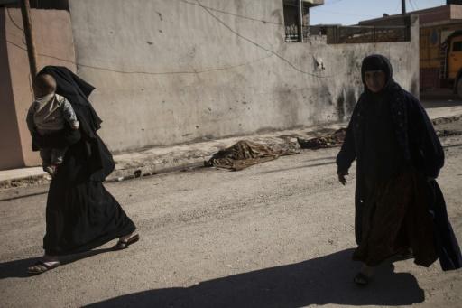 Des Irakiennes passent devant les corps de deux combattants islamiques dans les environs de Mossoul, le 19 novembre 2016 © Achilleas Zavallis AFP