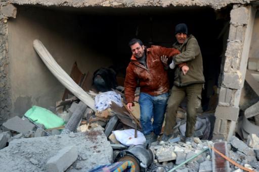 Deux hommes sortent des décombres après des bombardements aériens sur un quartier rebelle d'Alep, le 20 novembre 2016  © THAER MOHAMMED AFP