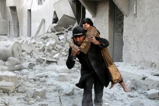 Un Syrien porte une femme sauvée des décombres après des frappes sur un quartier rebelle d'Alep, le 20 novembre 2016   © THAER MOHAMMED AFP