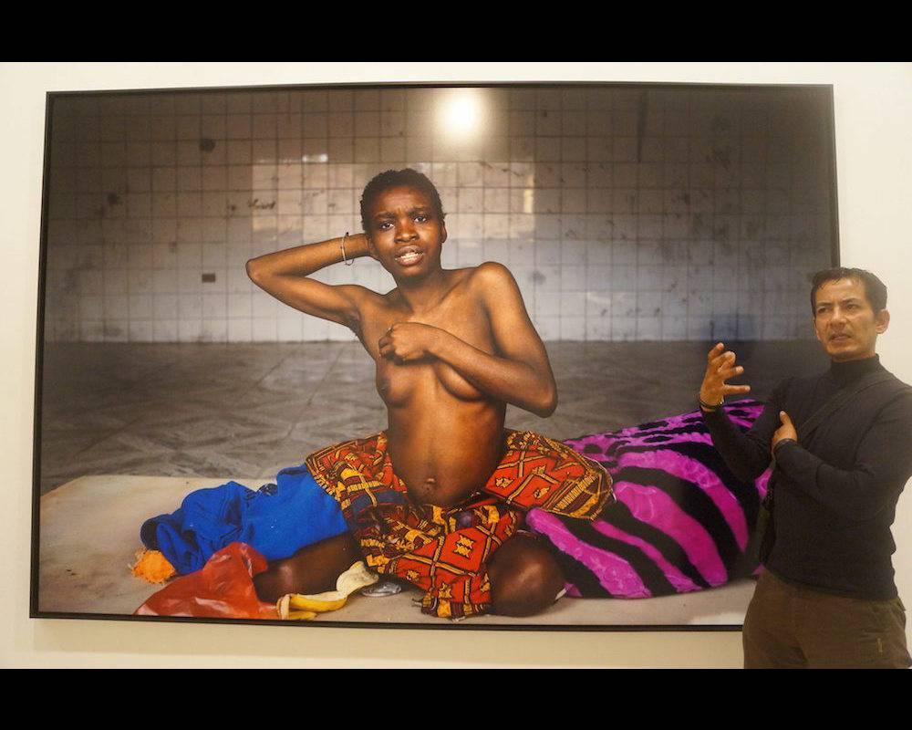 De février à juin 2016, Narciso Contreras, photoreporter, a enquêté sur le sort des migrants dans la Libye post-Kadhafi. Prix Carmignac du photojournalisme, le journaliste mexicain, également prix Pulitzer, est ici à Londres en mai 2017 à côté d'une photo de migrante, lors d'une exposition qui met en tout simplement en lumière cet odieux trafic d'êtres humains dont la Libye est le théâtre. ©  MARCELA GUTIERREZ / NOTIMEX