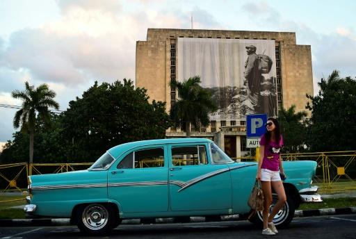 Une femme pose devant la librairie nationale sur laquelle est déployée une photo de Fidel Castro, le 27 novembre 2016 à La Havane © RONALDO SCHEMIDT AFP