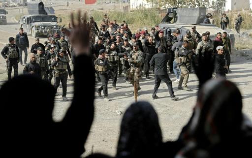 Des membres des forces spéciales irakiennes accueillis par la population dans un quartier reconquis de Mossoul, le 27 novembre 2016  © THOMAS COEX AFP