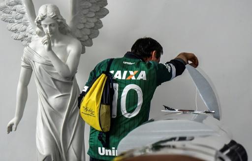 Roberto Di Marche, cousin d'un dirigeant de l'équipe, Nilson Folle Junior, tué dans l'accident, près d'un cercueil au funérarium de San Vicente à Medellin, le 30 novembre 2016 en Colombie © LUIS ACOSTA AFP