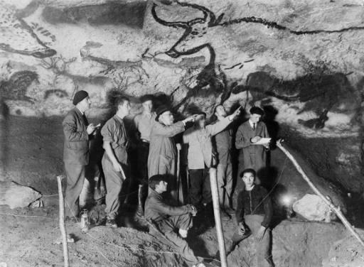 Le paléontologue et préhistorien Henri Breuil (3ème D) observe le panneau des aurochs dans la salle des taureaux de la grotte de Lascaux en 1948 à Montignac en Dordogne, en compagnie d'autres archéologues et de M. Ravidat (D, assis) et J. Marsal (G, assis). © - AFP/Archives